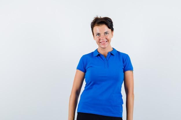 Starsza kobieta patrząc na kamery w niebieskiej koszulce i patrząc wesoło. przedni widok.