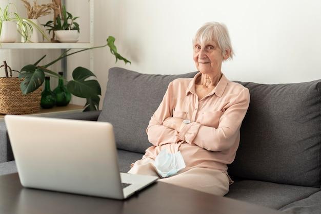 Starsza kobieta patrząc na laptopa w domu opieki