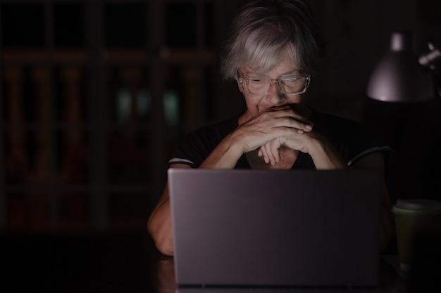 Starsza kobieta patrząca i używająca laptopa w domu późno w nocy, pracująca, oglądając filmy na komputerze