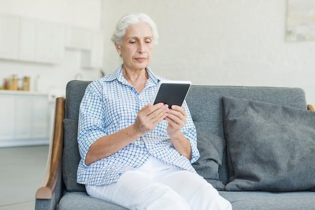Starsza kobieta patrzeje cyfrową pastylkę