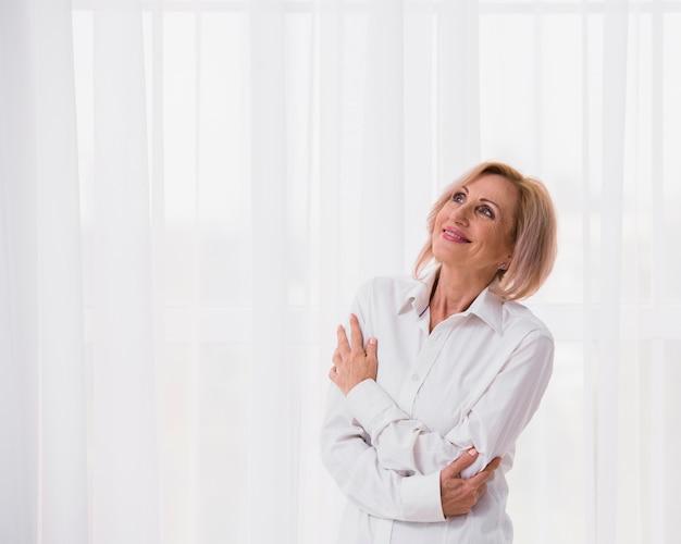Starsza kobieta patrzeje daleko od z kopii przestrzenią