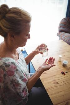 Starsza kobieta patrzeje jej medyków w ona ręki