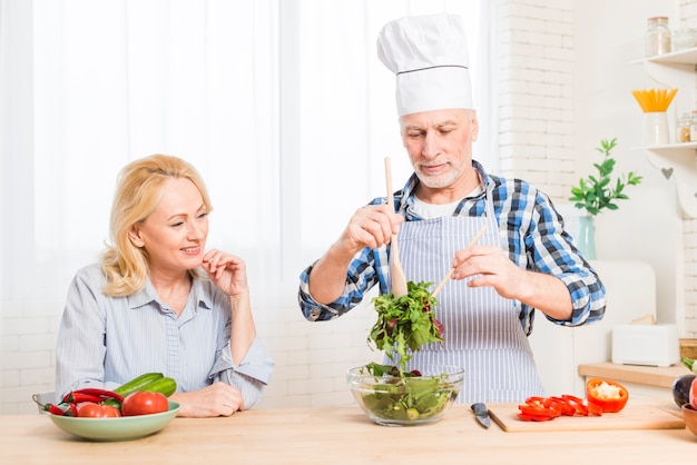 Starsza kobieta patrzeje jej męża przygotowywa sałatki w kuchni