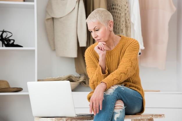 Starsza kobieta patrzeje pensively przy laptopem