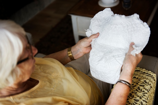 Starsza kobieta patrzeje pieluszkę