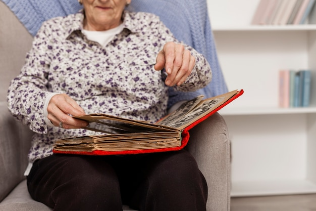 Starsza kobieta patrzeje w album fotograficznego