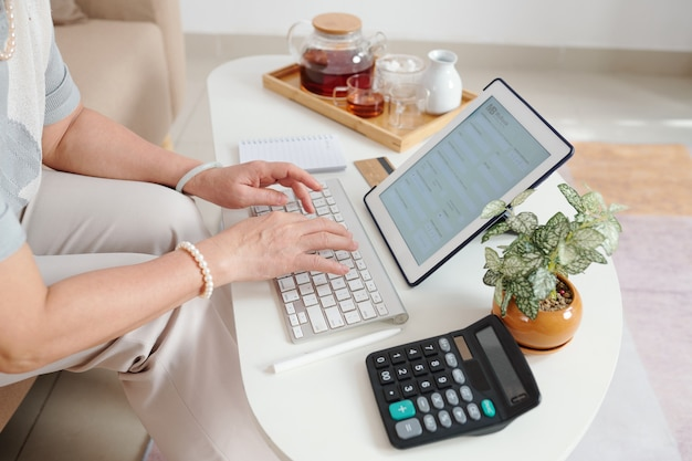 Starsza kobieta pijąca herbatę i wprowadzająca informacje bankowe w formie na cyfrowym tablecie
