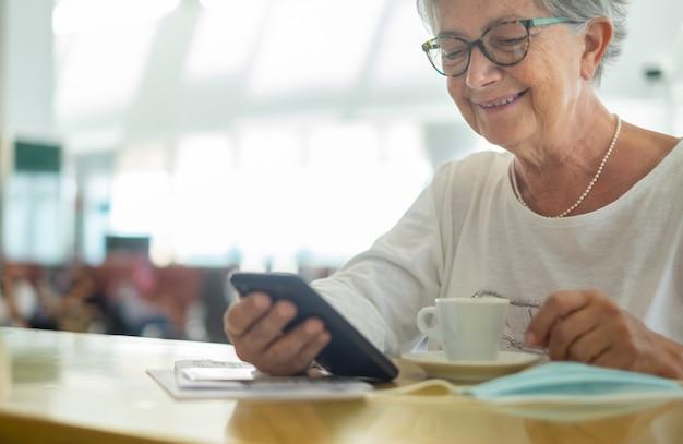 Starsza kobieta pijąca kawę i sprawdzająca swój telefon na lotnisku w oczekiwaniu na wejście na pokład
