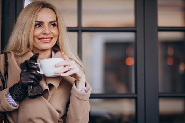Starsza kobieta pije kawę na zewnątrz kawiarni