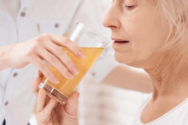 Starsza kobieta pije sok w szpitalu.