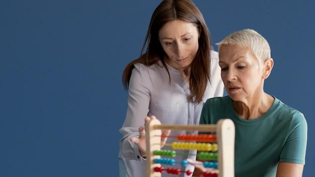 Starsza kobieta podczas sesji terapii zajęciowej z psychologiem z miejscem na kopię