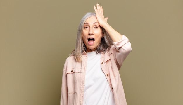 Starsza kobieta podnosząca dłoń do czoła, myśląc ups, po popełnieniu głupiego błędu lub przypomnieniu sobie, czując się głupio