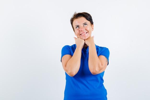 Starsza kobieta podpiera brodę na rękach w niebieskiej koszulce i wygląda rozmarzona. przedni widok.