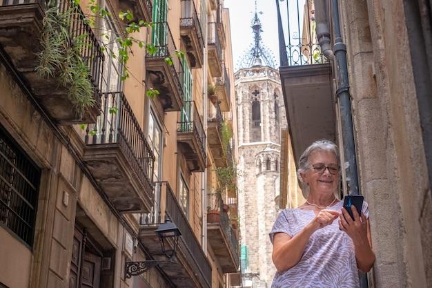 Starsza kobieta podróżująca po barcelonie korzysta z telefonu komórkowego odpoczywając. stara katedra w tle
