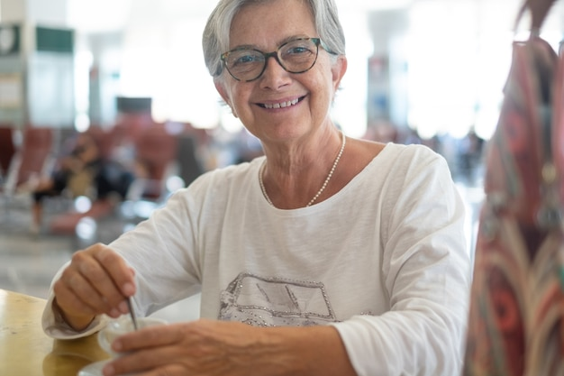 Starsza kobieta podróżująca uśmiechnięta pijąca kawę na lotnisku czekająca na wejście na pokład