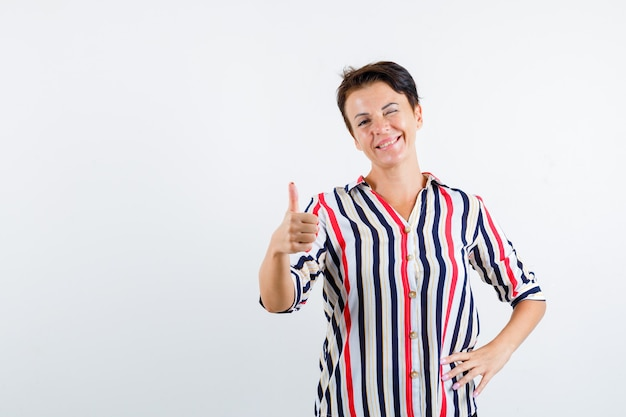 Starsza kobieta pokazując kciuk do góry, mrugając, trzymając rękę na pasie w bluzce w paski i wyglądając pewnie. przedni widok.