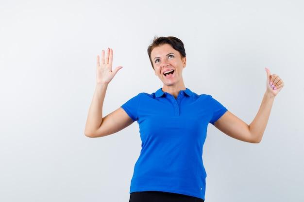 Starsza kobieta pokazuje dłoń i kciuk w niebieskiej koszulce i wygląda szczęśliwy, widok z przodu.
