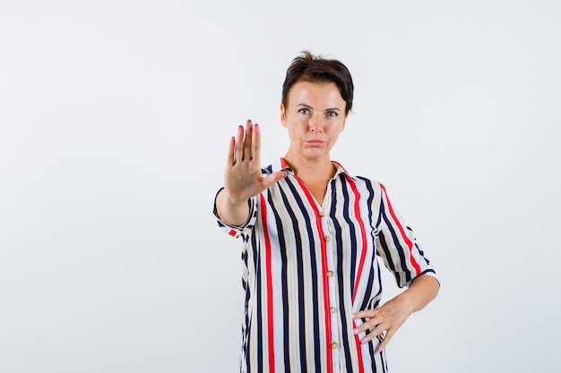 Starsza kobieta pokazuje znak stopu, trzymając rękę na pasie w bluzce w paski i patrząc poważny, widok z przodu.