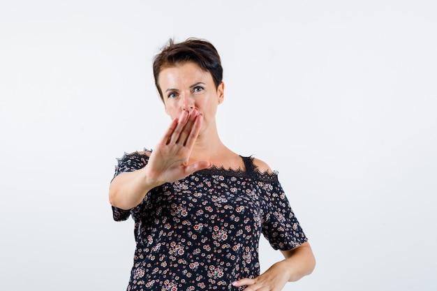 Starsza kobieta pokazuje znak stopu, trzymając rękę na talii w bluzkę w kwiaty, czarną spódnicę i wygląda pewnie. przedni widok.