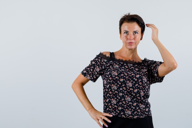Starsza kobieta, pozowanie, trzymając ręce w pasie w bluzce i patrząc atrakcyjnie, widok z przodu.