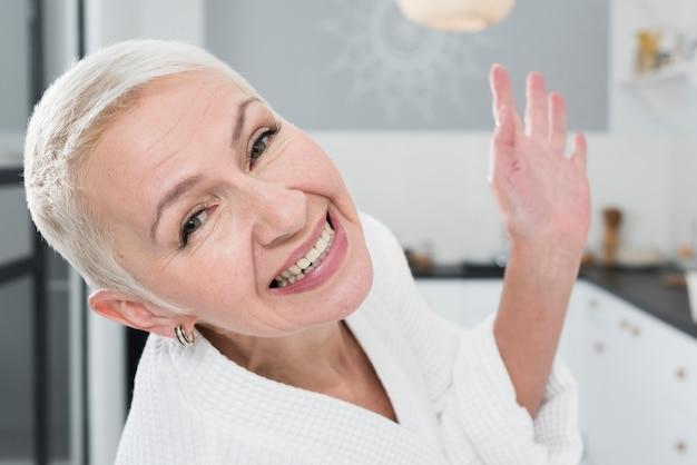 Starsza kobieta pozuje i ono uśmiecha się szeroko