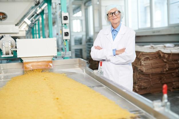 Starsza kobieta pozuje przy fabryką