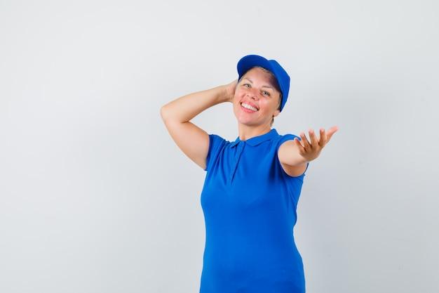 Starsza kobieta pozuje wyciągając rękę w t-shirt i patrząc wesoło.