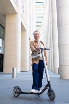 Starsza kobieta pozuje z elektryczną hulajnogą w mieście