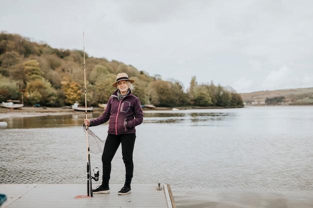 Starsza kobieta pozuje z wędką nad jeziorem