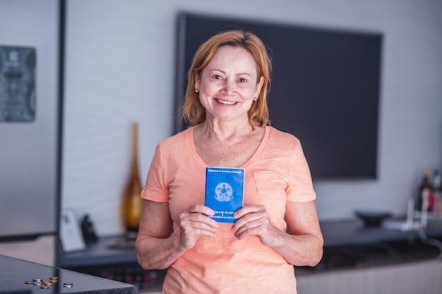 Starsza kobieta pracownik trzyma w ręku brazylijską kartę pracy. osoba starsza kobieta posiadająca brazylijską kartę pracy