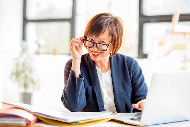Starsza kobieta pracująca z dokumentami i laptopem w jasnym, nowoczesnym wnętrzu biurowym