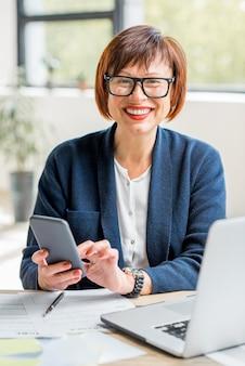 Starsza kobieta pracująca z dokumentami i smartfonem w jasnym, nowoczesnym wnętrzu biurowym