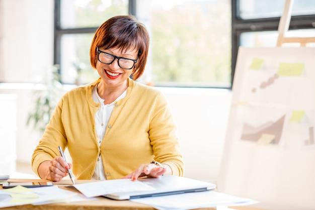 Starsza kobieta pracująca z dokumentami w jasnym, nowoczesnym wnętrzu biurowym
