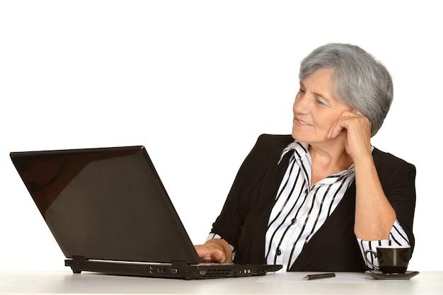 Starsza kobieta pracuje na laptopie na białym tle