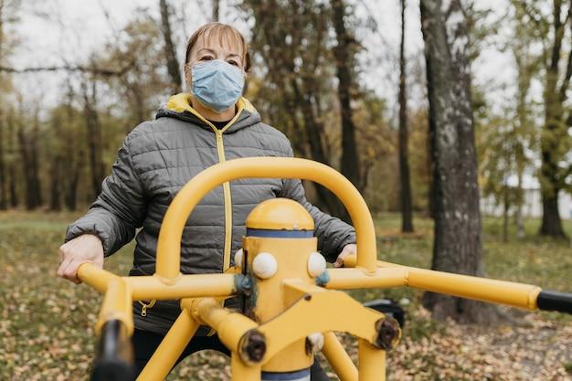Starsza kobieta pracuje na zewnątrz z maską medyczną