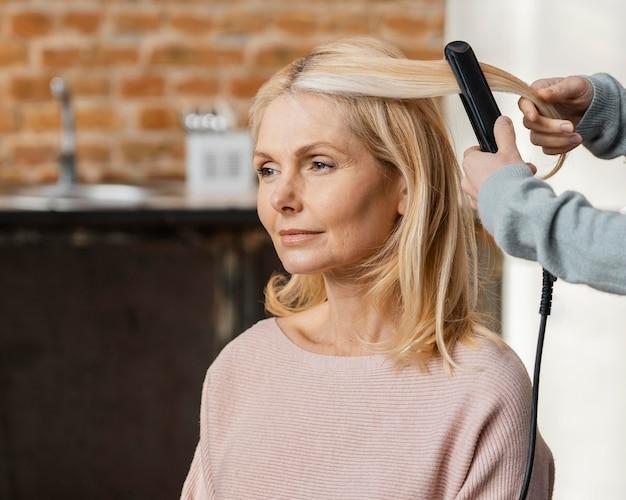 Starsza kobieta prostuje włosy przez fryzjera w domu