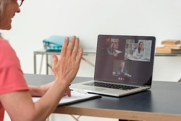 Starsza kobieta prowadzi rozmowę wideo na laptopie w domu