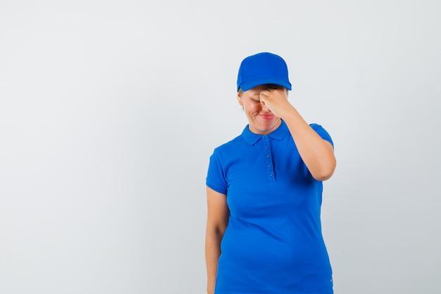 Starsza kobieta przeciera oczy i nos w t-shirt i wygląda na zmęczoną.