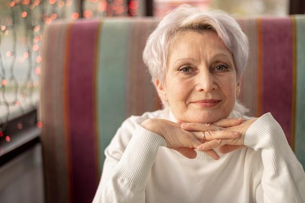 Starsza kobieta przy restauracyjnym obsiadaniem