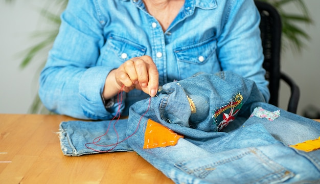 Starsza kobieta ręce do szycia na dżinsy tkaniny