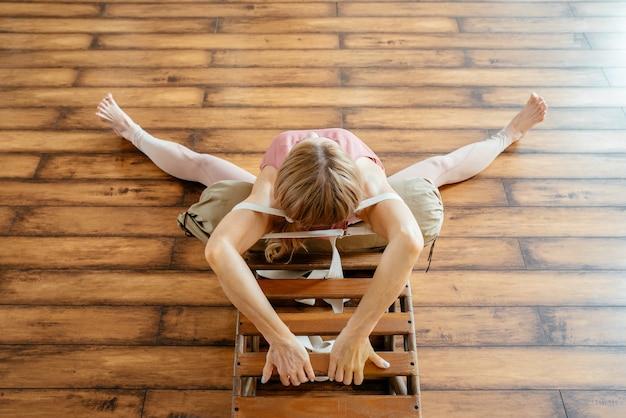 Starsza kobieta robi ćwiczenia rozciągające na ławce jogi backbend w studio
