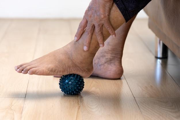 Starsza kobieta robi gumową piłkę do ćwiczeń palców dłoni, dłoni, dłoni i stóp z opiekunem.