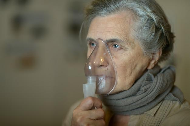 Starsza kobieta robi inhalację na ciemnym tle