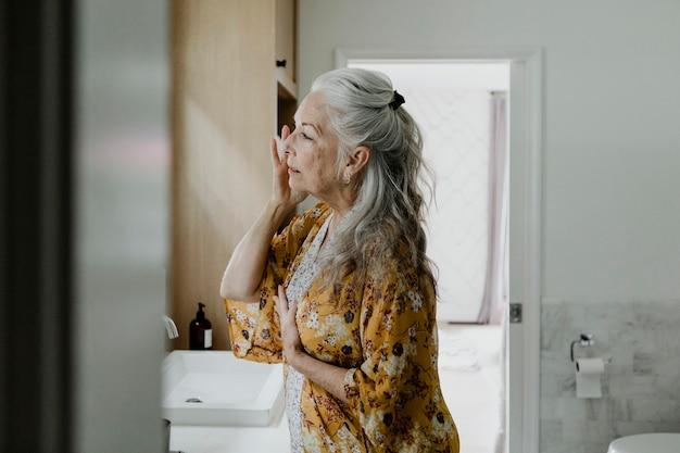 Starsza kobieta robi makijaż przed lustrem