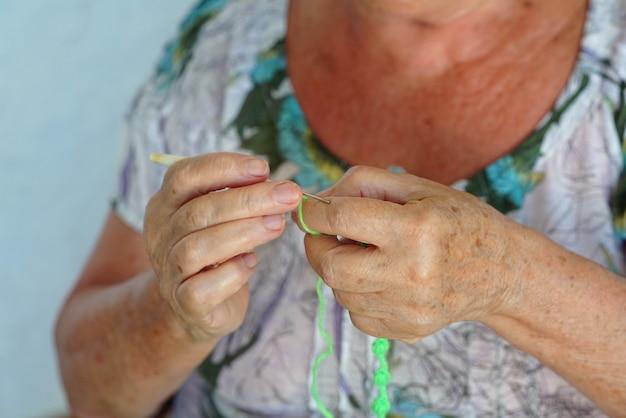 Starsza kobieta robi na drutach w wolnym czasie
