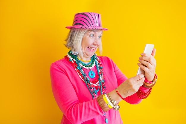 Starsza kobieta rozmawia na smartfonie w koncepcjach stylowych ubrań o seniorach