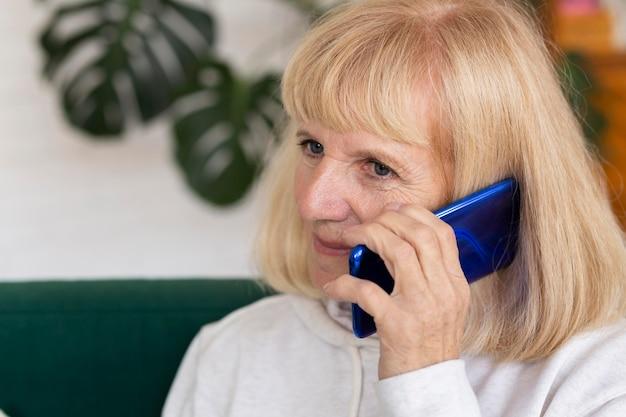 Starsza kobieta rozmawia przez telefon w domu