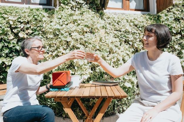 Starsza kobieta rozmawia z córką kobiety wody pitnej i relaksuje, rozmawiając na zewnątrz, uśmiechając się szczęśliwa koncepcja emerytury, dzień matki mother