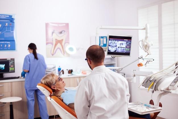 Starsza kobieta rozmawia z dentystą w gabinecie dentystycznym o problemie zębów, siedząc na krześle. opiekun medyczny do pielęgnacji zębów omawiający ze starszym kobietą higienę jamy ustnej.