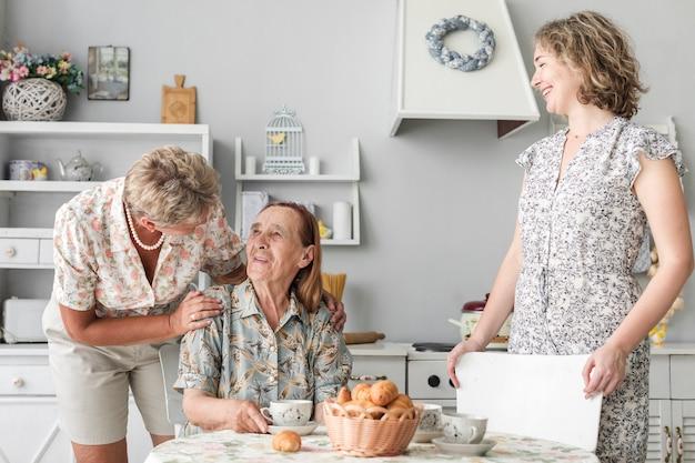 Starsza kobieta rozmawia z matką siedzi na krześle przed jej córką